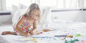 Little-girl-writing-on-a-bed-e1408629648638